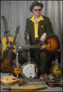 Photograph of me in a hat and yellow shirt, with about 8 or more instruments.